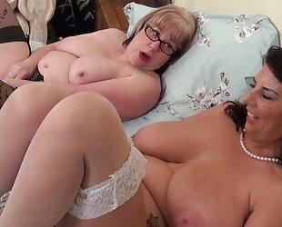 Two spunky matures with big tits playing lesbian games in bed